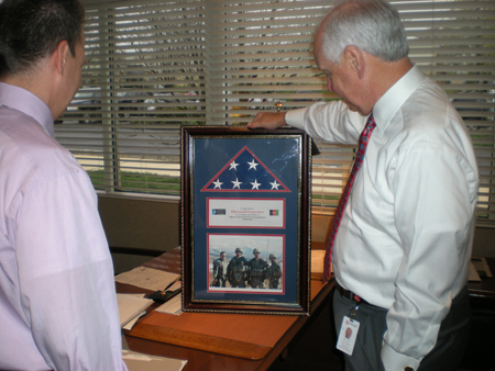 Community Involvement: President Bill Sautter and COO Jim Pizzi admire the framed flag